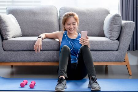 Beautiful Asian women smile and listen to music after exercising at home. Фото со стока