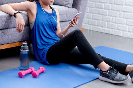 Asian woman listening to music and exercising at home