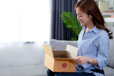 Asian women are happy and satisfied with the products ordered online. She is opening the box Banque d'images