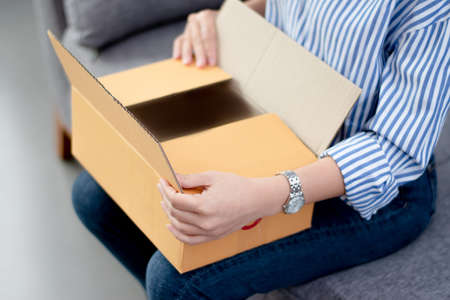 Asian woman is excited and happy to receive the products from the parcel. She is unpacking her gift box on the sofa at home. Online shopping concept.