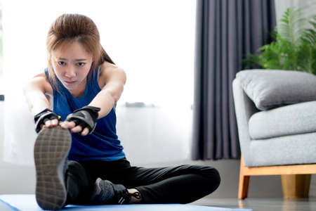 Asian women warm up before exercising at home. Workout from home.
