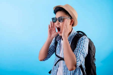 Happy Asian Backpackers. He is shouting open mouth for the copy space on a blue background.