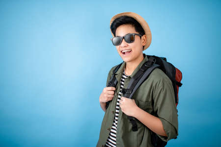 Asian backpackers are smiling and happy on the blue background in the studio.