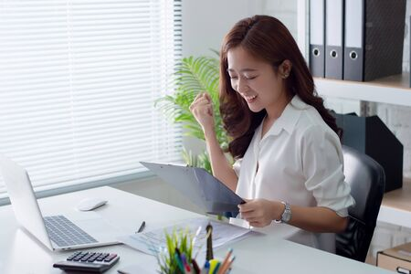 Beautiful young business woman is smiling and happy with the sales in the office.