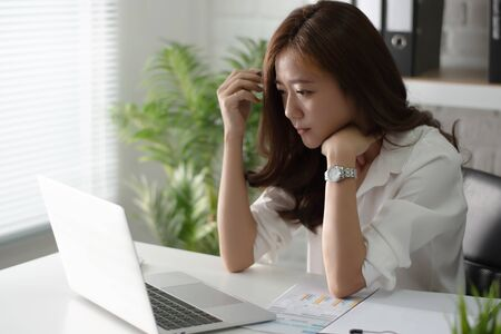 Asian businesswoman is thinking and planning about work at the office. Фото со стока
