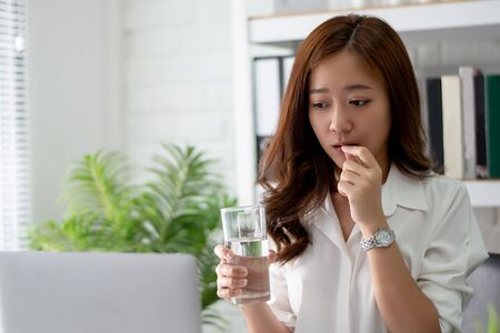 Asian business women drinking water and taking medicine. She feels sick.