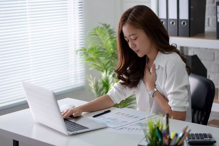 Asian working woman with heart disease, she is working hard in the office.