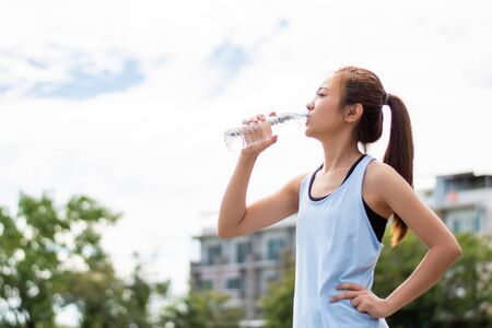 Asian women runners drinking water. She was tired after running.