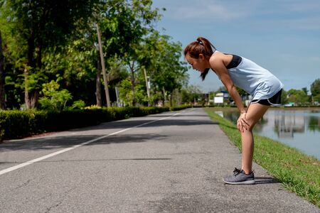 Asian women exercising. She is running on the street, she is tired and hot from the sun.