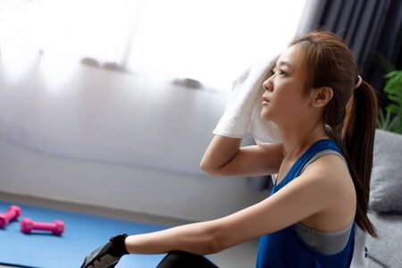 Young Asian woman exercising at home. She is tired and has sweat on her face.