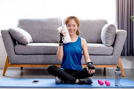 Young Asian woman wiping her sweat after a workout at home.