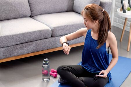 Young Asian woman is uploading her exercise activities on a smart watch at home. Фото со стока