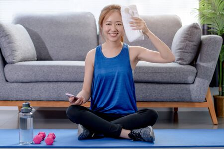 Young Asian woman wiping her sweat after exercise at home, workout at home.
