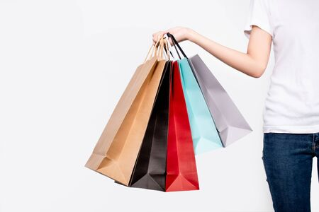 Young woman holding shopping bags on white background. Isolated background. Фото со стока