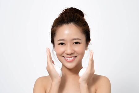 Beautiful Asian woman is using a facial foam to wash cosmetics off her face.