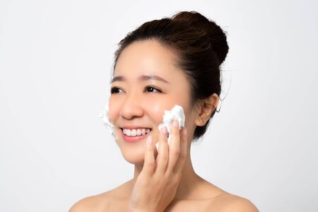 Close up face of beautiful Asian woman is using a facial foam to wash cosmetics off her face in the studio.