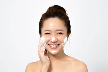 Beautiful Asian woman is using a facial foam to wash cosmetics off her face on a white background.
