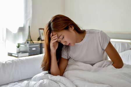 An Asian woman feels headache. She wakes up in the middle of the night while she sleeps in bed. Фото со стока
