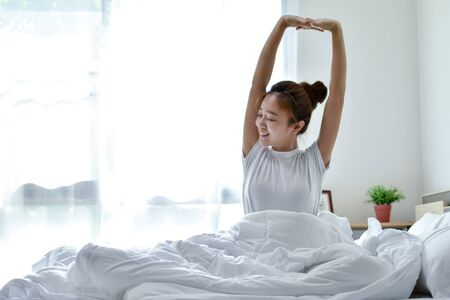 Beautiful Asian woman is happy to wake up in the morning on a bed. She felt very refreshed after a deep sleep all night.
