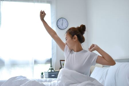 Beautiful Asian woman wakes up in the morning on a bed. She feels very fresh. Фото со стока