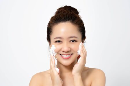Asian women are using foam to wash face in the studio.