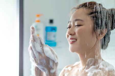 Asian women are taking a shower in the bathroom. She is using soap to rub her body.