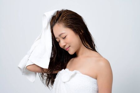 Asian women are using a towel to dry the hair. After she shower. Фото со стока