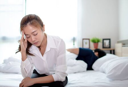 Young lovers, they are having problems with quarrel. Woman is sitting on the bed and she is having a headache with a problem.