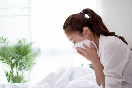 Business woman is sick and sneezing hard on the bed.