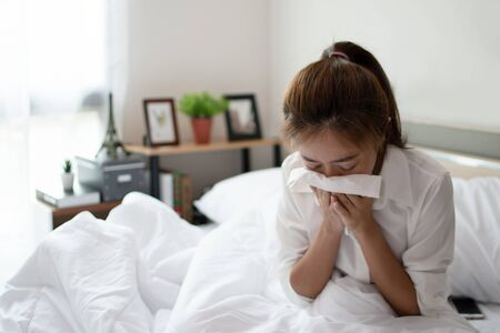 Young businesswoman is sick and coughs heavily on the bed in her room.
