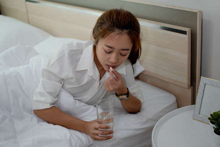 Asian women taking medication She is sick and unable to work.