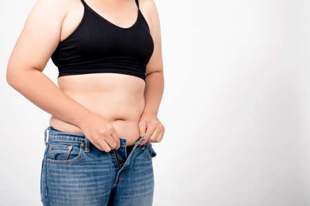 Asian women are overweight on a white background in the studio. Belly liposuction concept. Banco de Imagens - 150710562