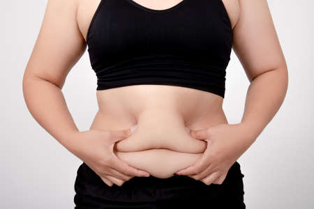 Asian women are overweight on a white background in the studio. Belly liposuction concept. Banco de Imagens