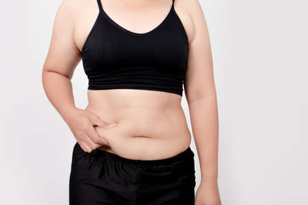 Asian women are overweight on a white background in the studio. Belly liposuction concept.