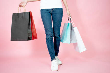 Asian women are happy to carry shopping bags in multiple colors in summer.