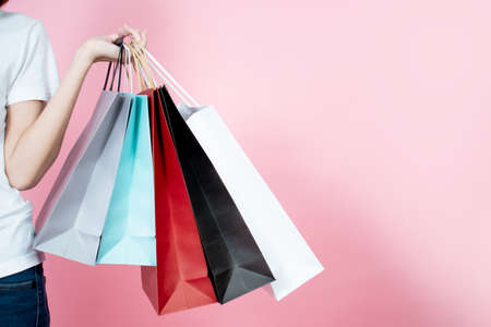 Happy women carrying summer shopping bagsม, isolated on pink background. Reklamní fotografie