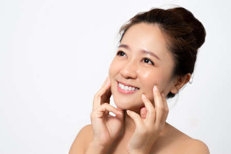 Close up face of beautiful woman asian in studio.  She touches her face.