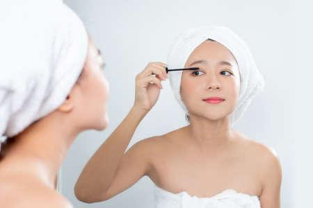 Asian beautiful women applying black mascara eyelashes in front of a large mirror.