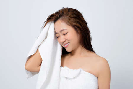 Beautiful Asian women are happy to use dry towels to dry their hair on a white background in the studio.