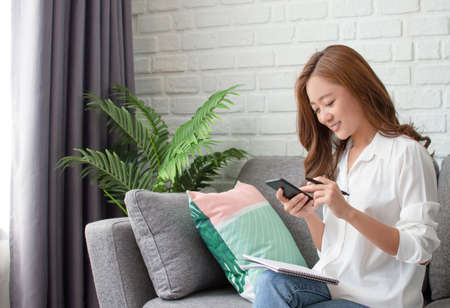 Asian women are relaxingly working at home. She using phone to contact people.