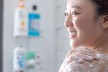 Close up of the face of an Asian woman taking a shower in the bathroom.