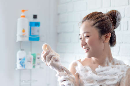 Beautiful woman taking shower in her bathroom. She is very happy.