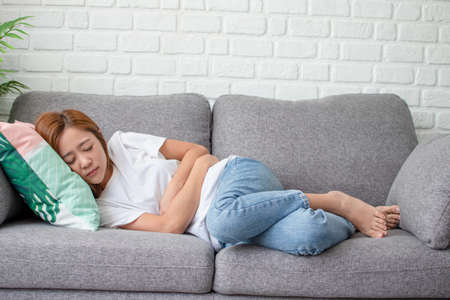Asian woman is sleeping, touching his stomach with his hands. She has menstrual pain on the sofa.