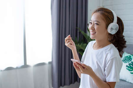 Asian woman was listening to music and singing a melody in the living room. She is very happy.