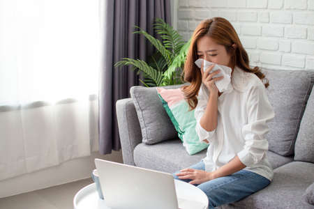 Asian women are sneezing and coughing.  She didn't go to work because she was sick. Reklamní fotografie