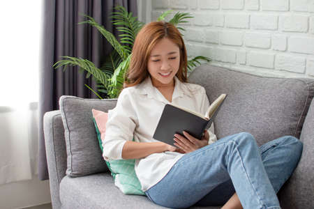 Smiling asian woman reading book at home. She is relaxing on the sofa.