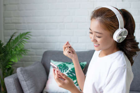 Beautiful Asian woman smiled happily while listening to music in the room. Reklamní fotografie
