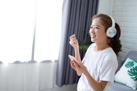 Happy Asian woman is listening to music and singing in the room.