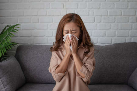 Asian woman are sneezing and working at home. She uses a tissue to cover her mouth.