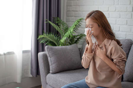 Asian woman sneezing and using tissue to cover her mouth.